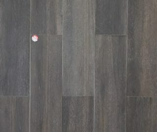 """8"""" x 45"""" porcelain plank tile that looks like hardwood. This tile is dark brown color with some grey graining."""