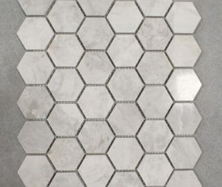 """White and grey marble mosaic in 2""""x2"""" diameter hexagons for shower floors."""
