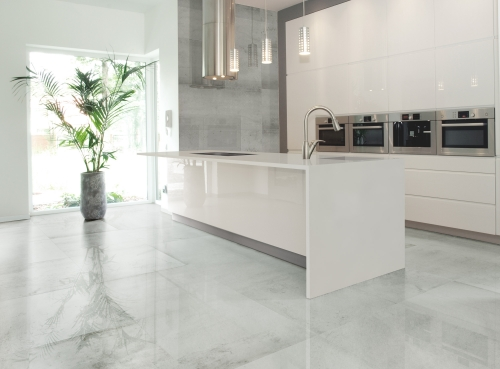 Porcelain floor tile with concrete effect Sassari Pear in light Grey color with a polished finish in 24x48 large rectangle format in kitchen with white counter top