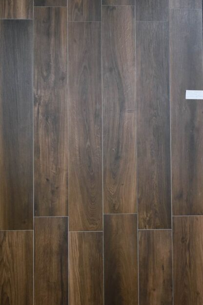 Wood look porcelain tile from Spain in dark brown color with some red hues for a warm style interior flooring.