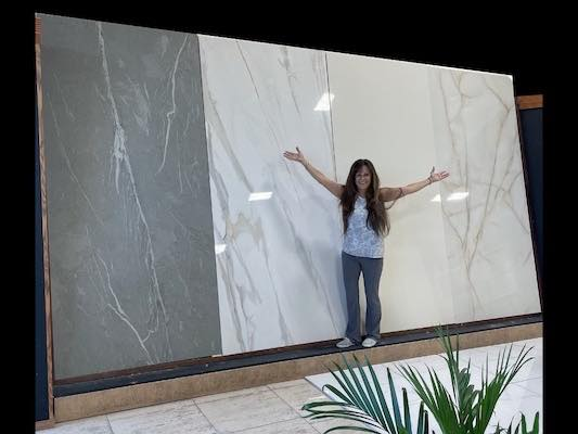 PICTURE OF SALES MANAGER IN FRONT OF PORCELAIN SLABS TO GIVE AN IDEA ABOUT THE IMMENSE SIZE OF THE SLABS